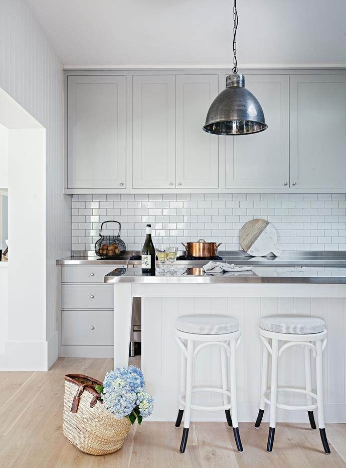 "This [modern shaker country home](https://www.homestolove.com.au/modern-shaker-country-home-13758|target=""_blank"") features a pared-back palette of blonde timber flooring and crisp white walls throughout. In the kitchen soft grey shaker-style cabinets add a subtle contrast to the white subway tiled splashback."
