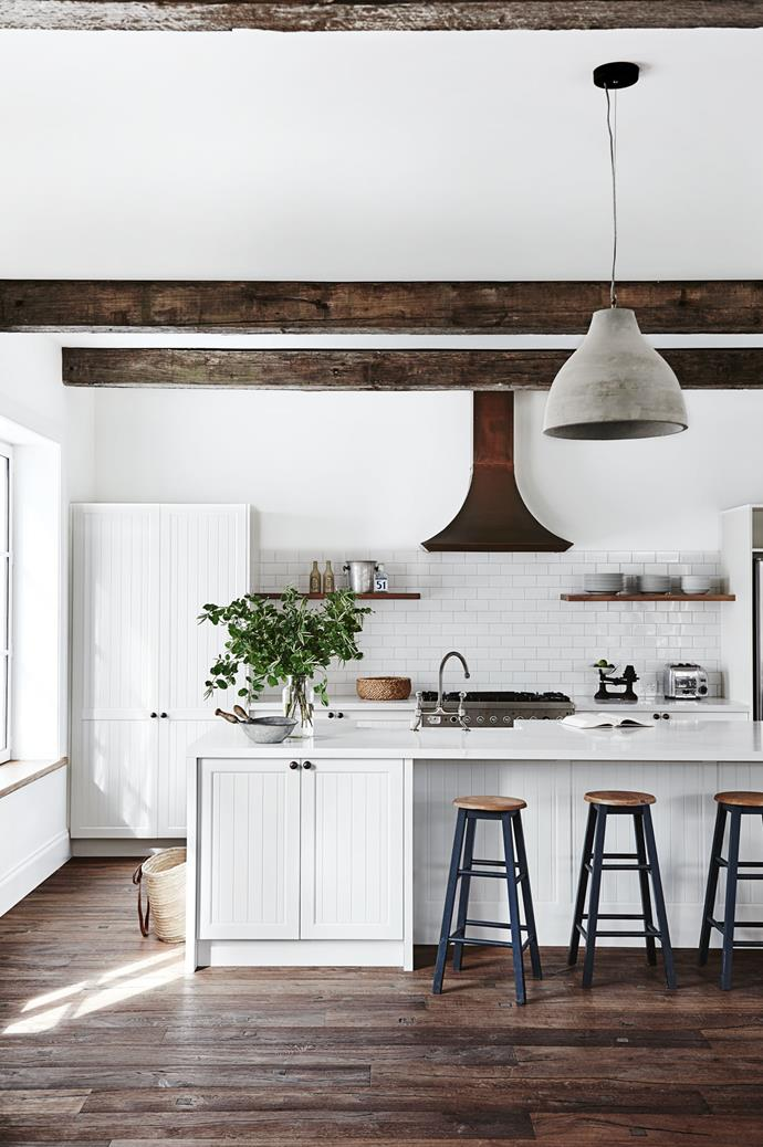 "Inspired by French Provincial style, [this Victorian farmhouse](https://www.homestolove.com.au/french-provincial-farmhouse-trentham-12156|target=""_blank"") features weathered timber flooring throughout. In the kitchen, white panelled shaker style kitchen cabinetry adds a bright contrast, as does the copper rangehood."