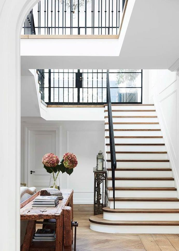 """The elegant entryway in this [Gothic revival home](https://www.homestolove.com.au/gothic-revival-home-19307 target=""""_blank"""") stops you in your tracks. With its juxtaposition of modern and traditional – a flowing wrought-iron balustrade and classic wall panelling teamed with industrial steel-framed windows and skylight – it could belong in a Belle-Époque Parisian townhouse."""