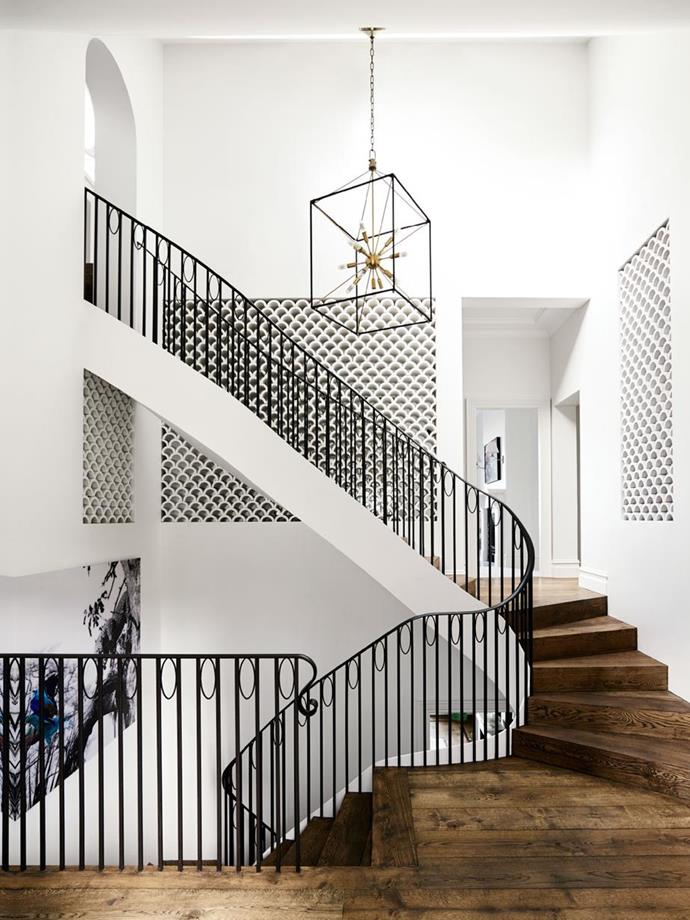 """A sculptural staircase that descends to the open-plan main living area below was a key design of this [Spanish mission style home's Hollywood glamorous update](https://www.homestolove.com.au/a-spanish-mission-style-homes-hollywood-glamour-update-6677