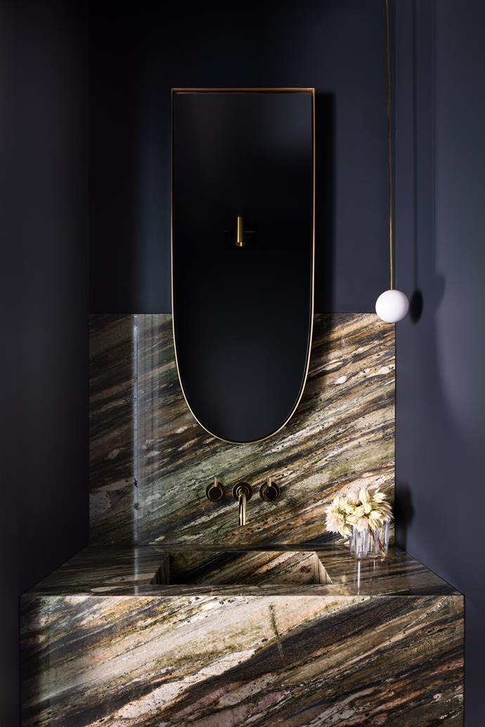 A custom vanity designed by Decus Interiors makes a bold statement in this glamorous and moody space. It features polished 'verde fashion' natural stone from WK-Quantum Quartz.