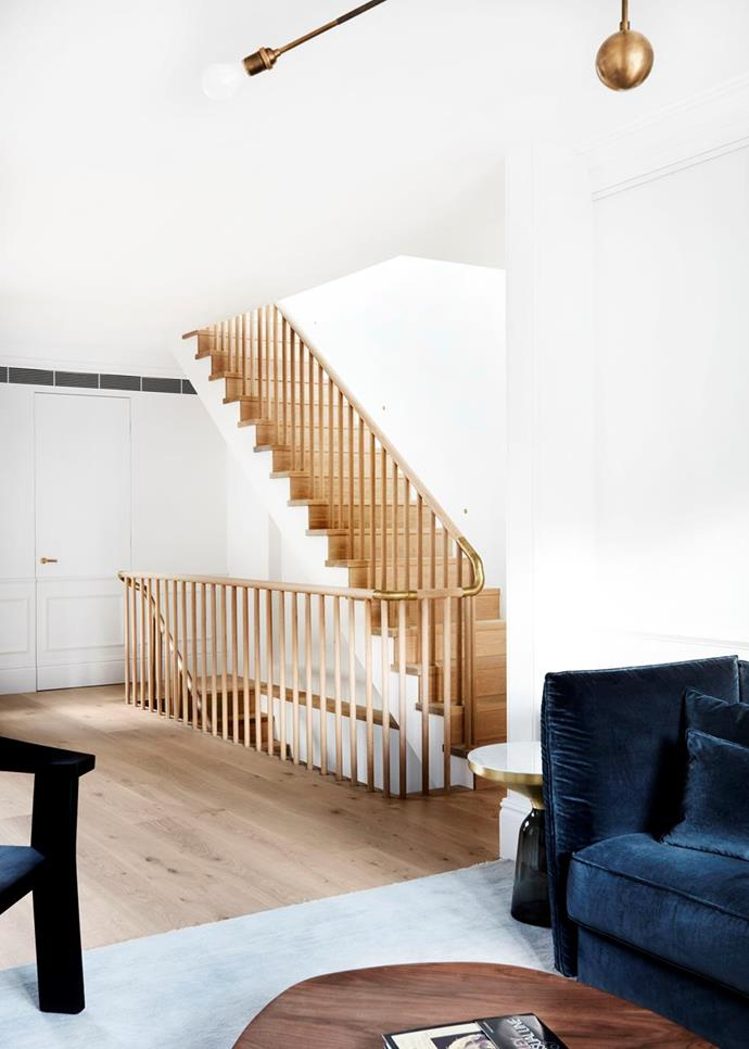 """The stairwell and formal living area of this [revamped Sydney terrace](https://www.homestolove.com.au/a-revamped-sydney-terrace-with-a-tranquil-aesthetic-19031 target=""""_blank"""") has a tranquil aesthetic thanks to Freado oak floorboards and stairs from Tongue N Groove. Balustrade in solid oak with custom brass details."""