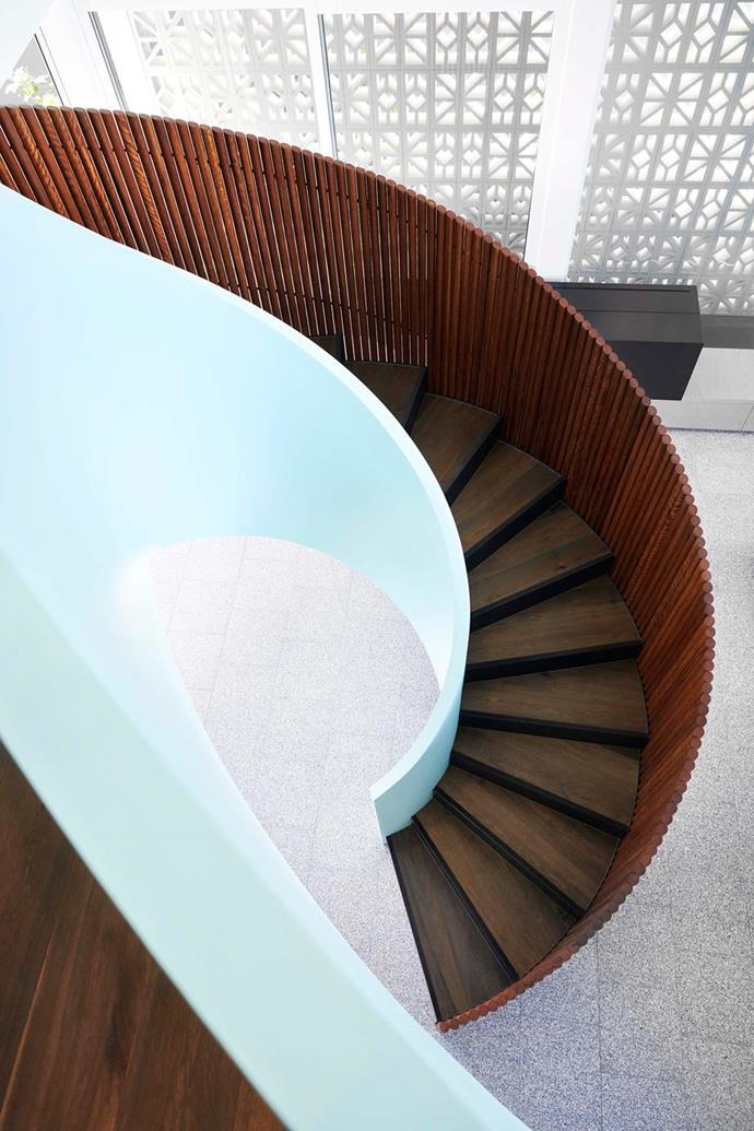 """Blue timber battens frame the spiralling internal staircase in a [Palm Springs inspired beach house in Noosa](https://www.homestolove.com.au/palm-springs-style-beach-house-19258