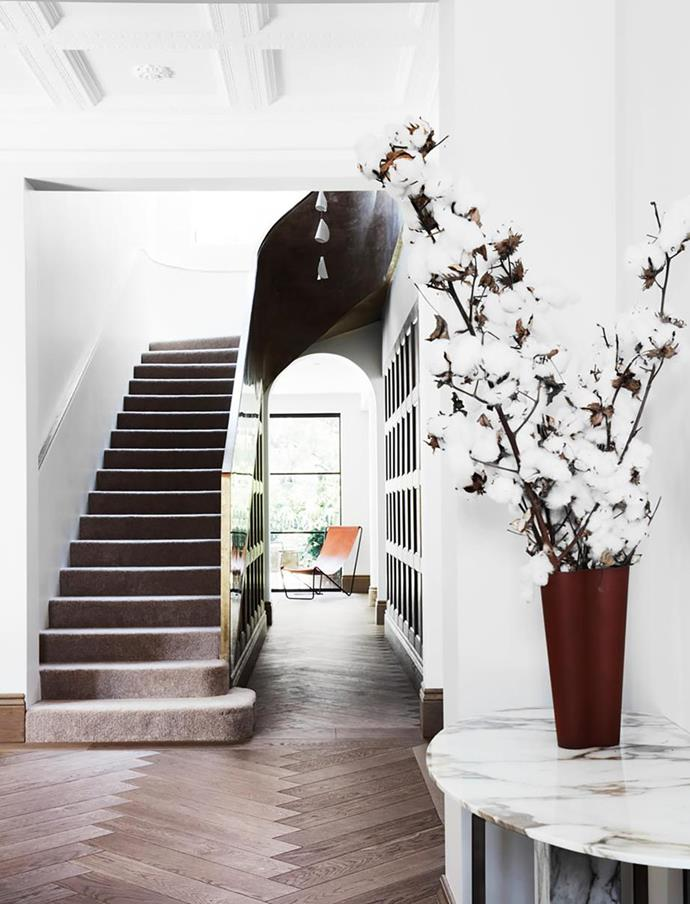 """The stairwell of this [heritage home in Sydney's eastern suburbs](https://www.homestolove.com.au/heritage-property-fashioned-into-elegant-house-20094 target=""""_blank"""") is the central spine of the home, and is finished in white and putty-coloured stucco lustre with a handcrafted brass rail and natural alpaca carpet on herringbone Mafi flooring."""