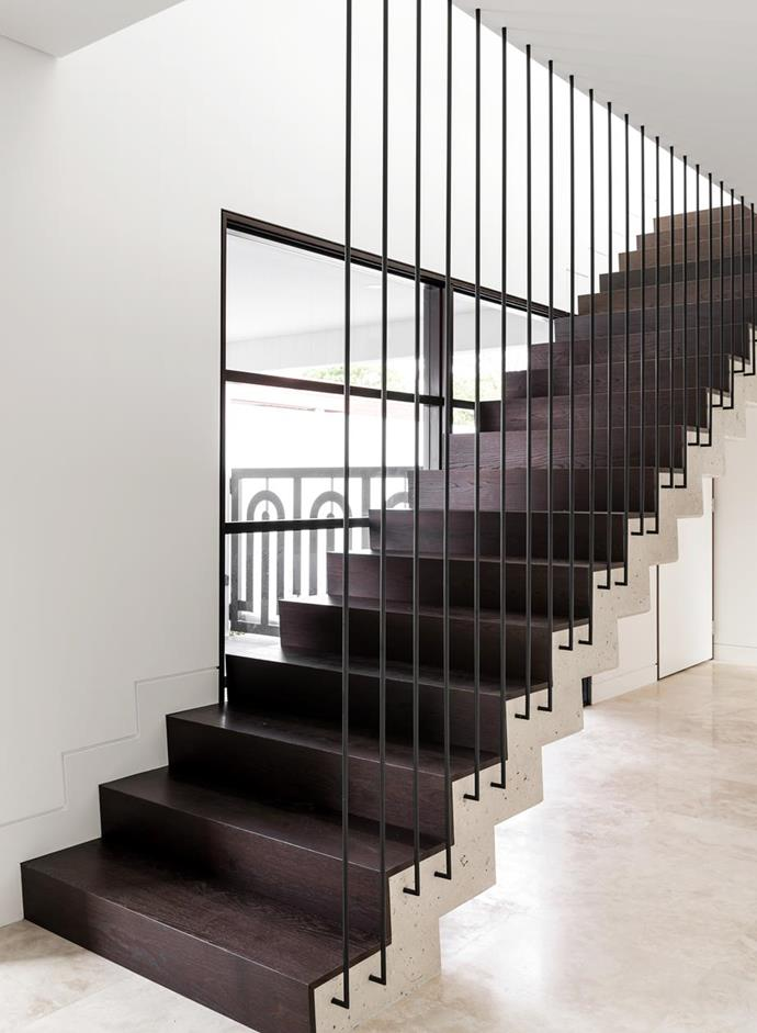 """The white-concrete stairs, custom--designed steel balustrading and treads made from stained oak ramp up the glamour in a [family home that blends Italian design and Art Deco style](https://www.homestolove.com.au/art-deco-home-italian-sensibility-20446
