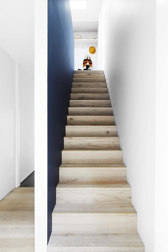 """A staircase with a feature wall in Whale Watching from Porter's Paints and Woodcut 'Sandwashed' floorboards with custom brass nosing welcomes guests in this [disused garage which was transformed into a luxe guest retreat](https://www.homestolove.com.au/converted-garage-guesthouse-21350 target=""""_blank"""")."""