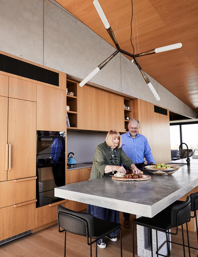 Elaine and Andrew in the spacious entertainer's kitchen. American oak-veneer joinery. G4 kitchen mixer, Zip Hydrotaps. Pendant light, Christopher Boots. Dita stools, Grazia & Co. Polished concrete benchtops. Caesarstone splashback in Sleek Concrete. Stove and ovens, V-Zug. Liebherr fridge.