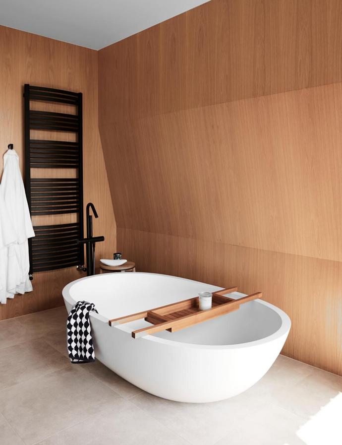 Haven composite-marble bath, Apaiser. Mizu 'Soothe' tapware and heated towel rail, all Reece. Wall cladding, Ameri can-oak veneer. Floor tiles, Lifestiles.
