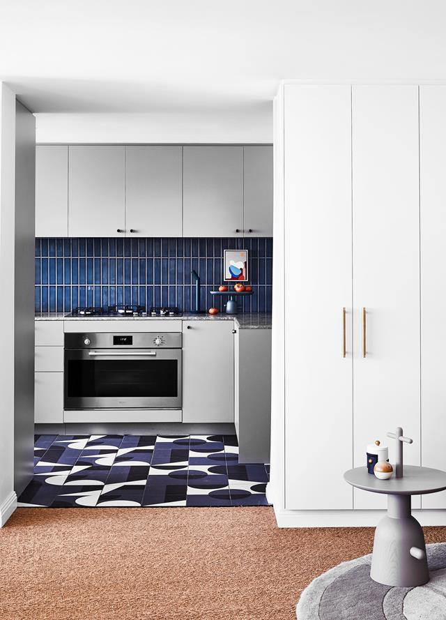 "Geometric tiles add a fun and dynamic element to this small kitchen. The renovation of this [apartment](https://www.homestolove.com.au/colourful-penthouse-apartment-with-personality-20466|target=""_blank"") saw Strutt Studios opt for rich blue and beige tones to mirror the harbour views."