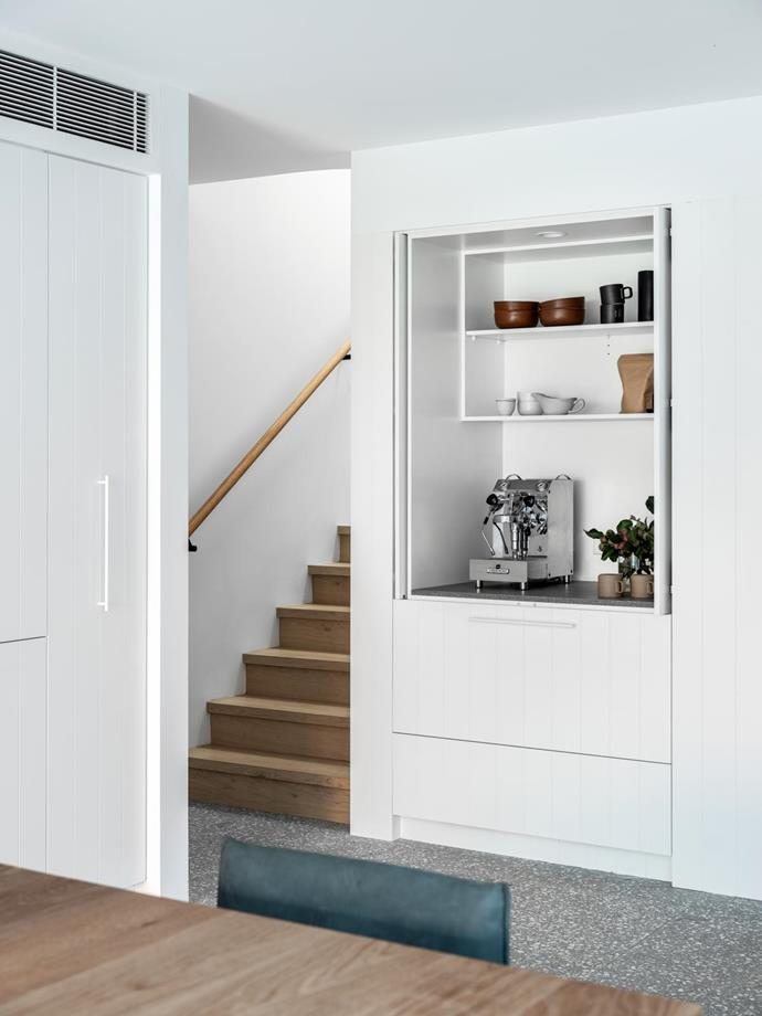 A built-in cabinet next to the stairs includes a fridge drawer – 