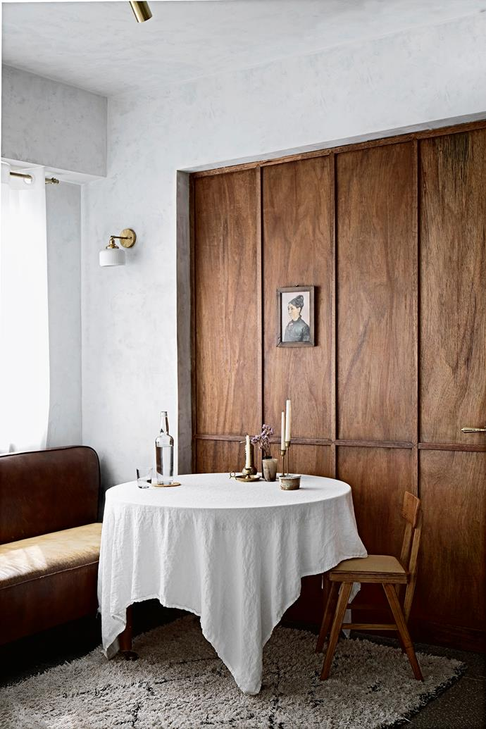 The couple eat together in this elegant dining space. They made and hand-stained the plywood wall while all of the furniture, including the banquette, is from makers in China.