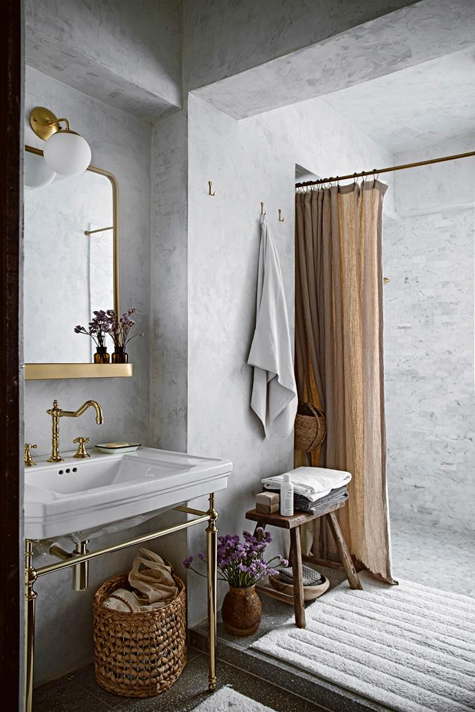 Those textural plaster-finished surfaces and sophisticated brass accents continue throughout the bathroom. A woven basket, wall hooks and vintage stool bring storage and visual warmth to the compact space. The towels are Ikea; the shower curtain is custom made.