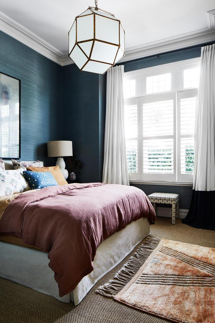 A blue grasscloth wallpaper from Milgate brings texture to the walls of Luke and Terri's bedroom. Plantation shutters by Think Shutters. Curtain by Bloom Bespoke. Seagrass flooring by Floorspace. Artwork by Anastasia Wiltshire.