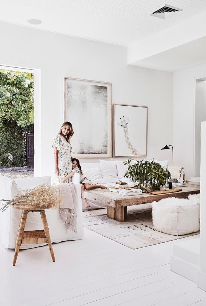 """The rushed white slipcovered sofa, timber coffee table and natural accessories in this [stylist's modern rustic home](https://www.homestolove.com.au/modern-rustic-interior-design-21024