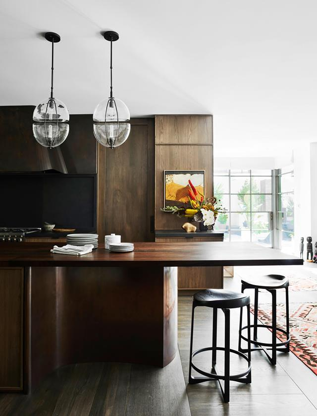 "Dark timber joinery in this open-plan kitchen pops against the backdrop of white walls and ceiling. The [coastal home](https://www.homestolove.com.au/luxurious-coastal-home-with-australian-art-21172|target=""_blank"") was given an elegant revamp by Alexandra Donohoe Church, principal of Sydney-based Decus Interiors."