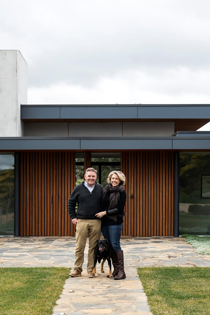 Steve and Fiona Green and their kelpie Tom at the main entrance of their home, which combines a steel and glass structure with two pavilions with stone found in the ruins on a neighbouring paddock. The original rafters now frame the front door.