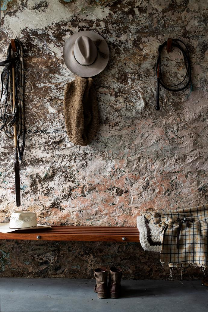 The mud room wall still bears traces of its previous life with remnants of old paint. The bench is made of rosewood timber and an Akubra hangs on the wall.