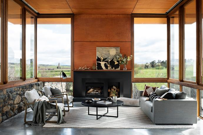 A made-to-order sofa, armchairs from Coco Republic, and tables from Globe West go well with a rug from Armadillo & Co. The ceiling is finished in hoop pine veneer plywood. Raincows by Alan Healy sits on the mantel above the Heatmaster fireplace.