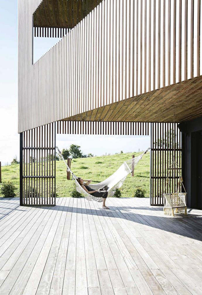 """Initially, the couple based themselves on the south coast of NSW where David had a house, but the long-term plan was to be back in Byron. """"We wanted to raise our children in the Byron Bay area, with its warm weather, abundance of amazing organic food, and the awareness and creativity of the people living here,"""" says Yvonn. They found a 1970s two-storey double-brick house with a sound structure and ideal location at the peak of the 2009 GFC.<br><Br>**Deck** Homeowner Yvonn enjoys the great outdoors from a sunny spot in a hammock from local shop Sweet Papillon."""