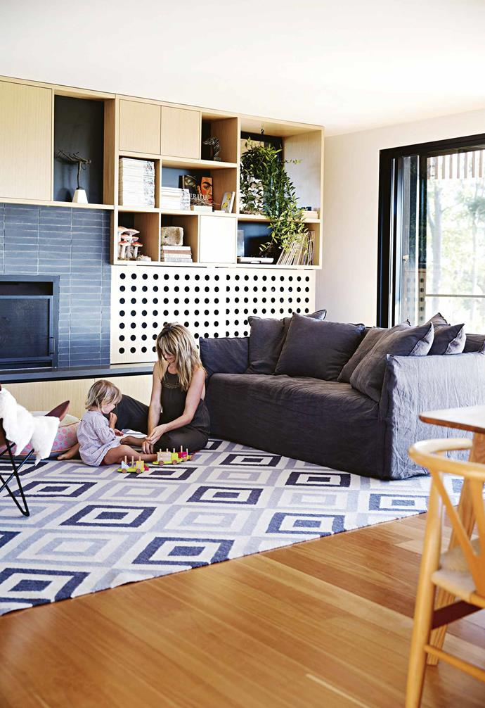 """The footprint of the house was maintained and the couple added a deck and staircase at the back, as well as flipping the living spaces. Originally, the house had the kitchen and dining areas upstairs with the bedrooms located downstairs.<br><br>**Living area** Matilda enjoys hanging out on the [daybed](https://www.homestolove.com.au/indoor-daybed-ideas-21303 target=""""_blank""""). The joinery was designed by David and holds books and treasures. Featuring unique circle cut-outs, the sliding doors were originally made to disguise the TV, but now keep firewood handy in winter."""