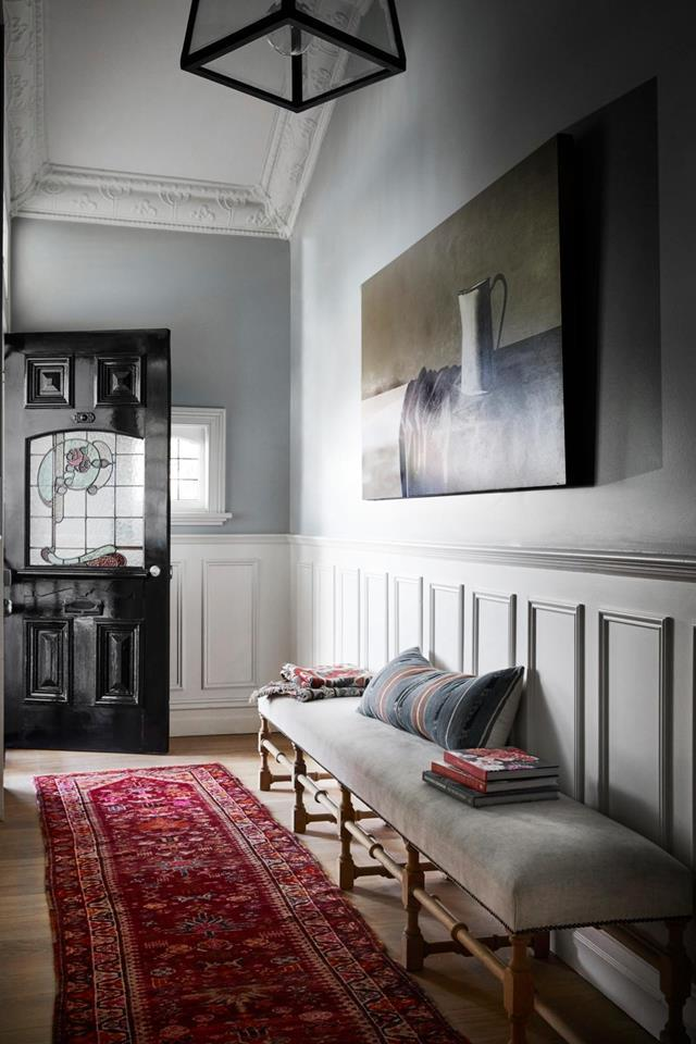 """The moody entryway of this [weatherboard home](https://www.homestolove.com.au/renovated-white-weatherboard-home-melbourne-21530 target=""""_blank"""") embraces its classic features including a stained glass window in the front door, and detailed cornice work. An artwork by Claire Stening ties in seamlessly with the space."""