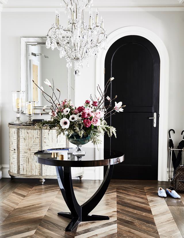 "The entry foyer of Ben Palmer and Josh Penn's [Art Deco apartment](https://www.homestolove.com.au/art-deco-apartment-gets-a-hamptons-style-makeover-1-20999|target=""_blank"") features new timber flooring, laid in a chevron pattern, and an array of beautiful antiques – an heirloom inlay cabinet and sparkling chandelier to name just two."