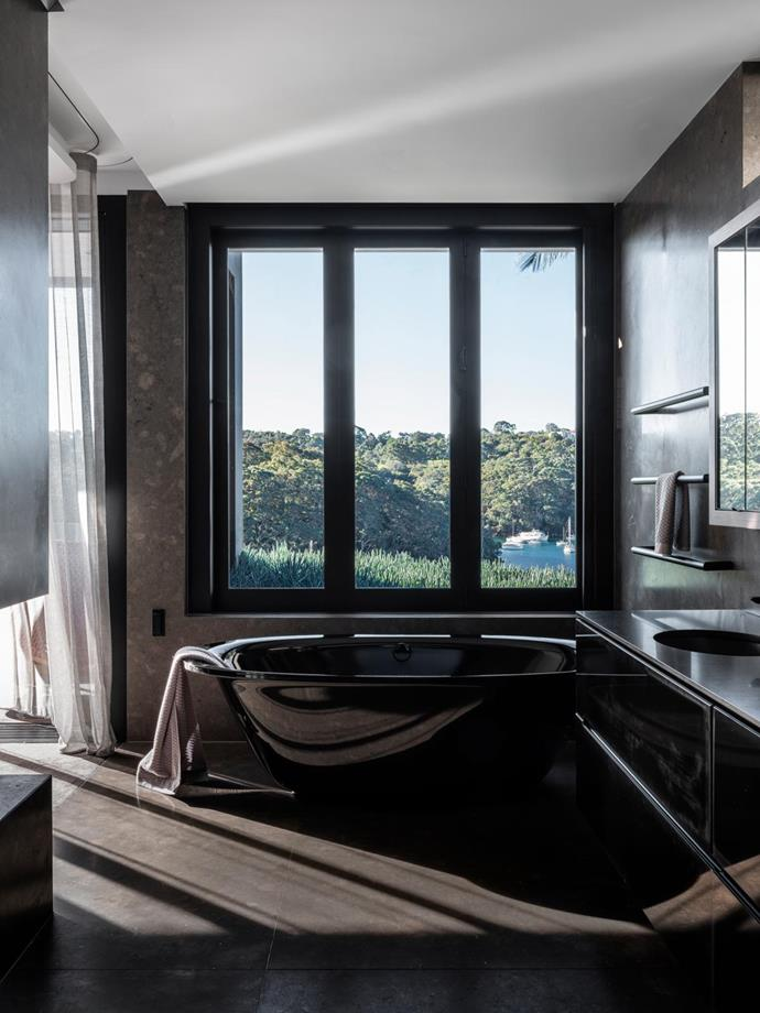 Kaldewei 'Ellipso' Duo bath in Black and Phoenix 'Vivid' slimline shower rails in Black, all Reece. Pietra Bronzea wall and floor tiles, World Stone. Custom vanity with glass fascia. Corian benchtop in Deep Nocturne C.