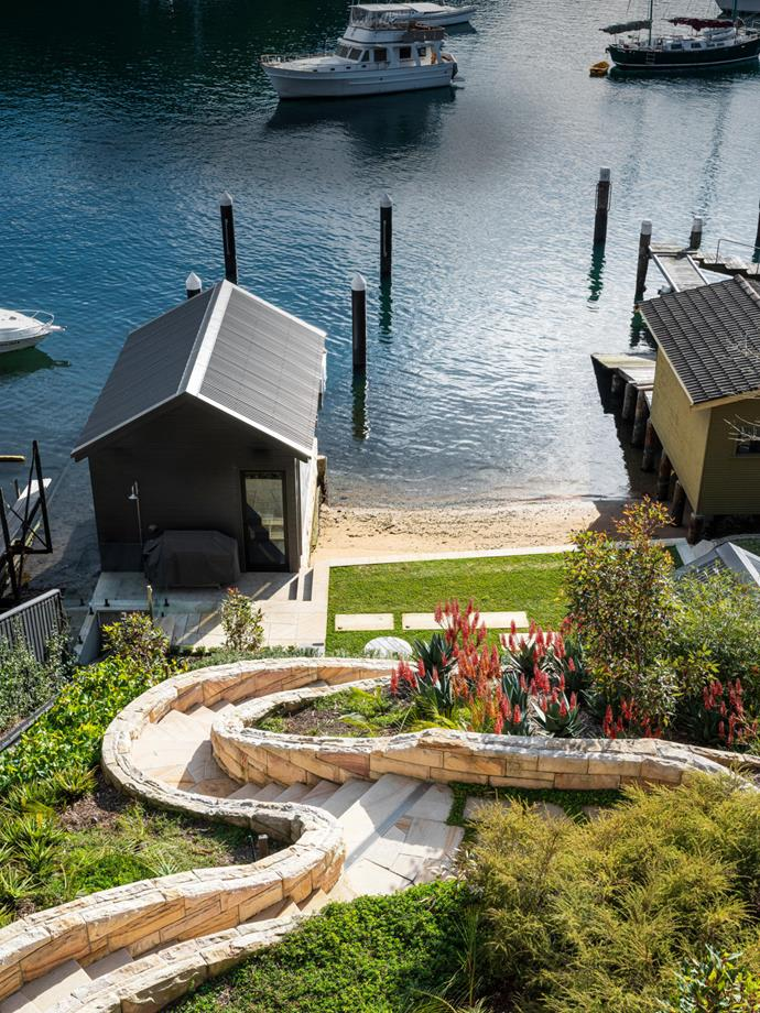 Sandstone steps lead down to the boat shed and firepit. Gardens designed by William Dangar and installed by Redefine Landscape Design. Robust, low-maintenance plants were selected to suit the coastal location.