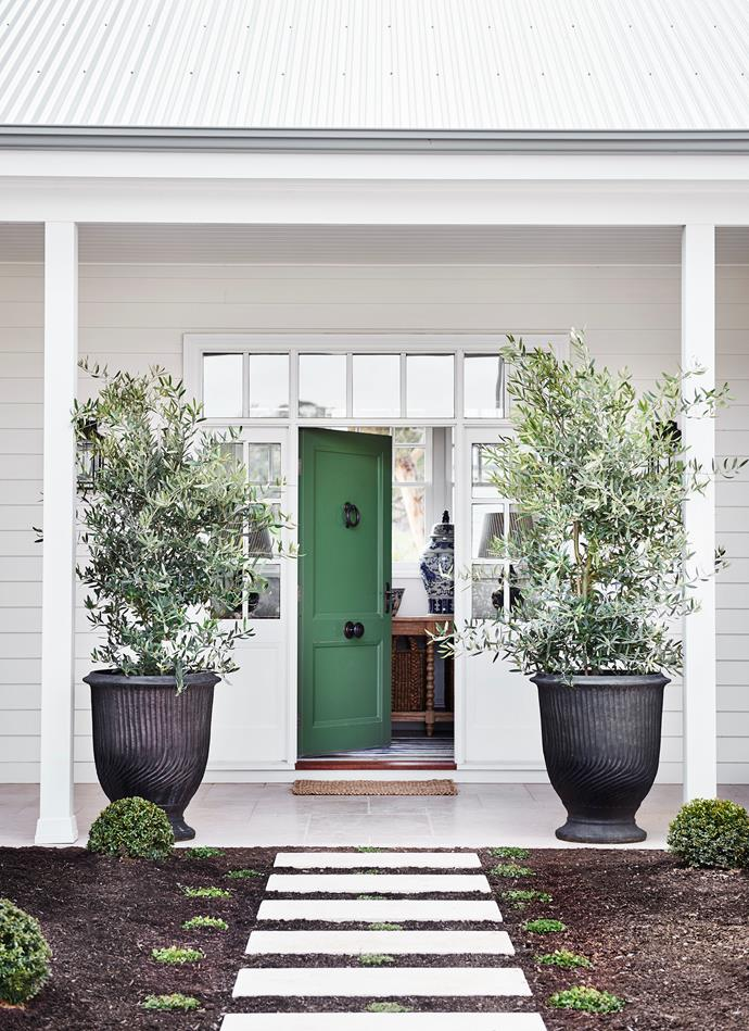 At the entrance to the family's home are urns from Julian Ronchi Garden Design and Nursery. The front door is painted in Porter's Paints 'Bayleaf'.