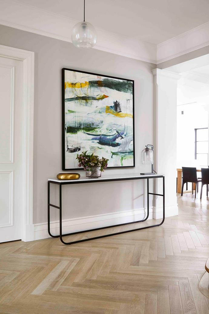 In the light-filled hallway, all eyes are drawn to the evocative artwork, 'Skate' by Michael Rich, above a Grazia & Co 'New York' marble-topped console table.