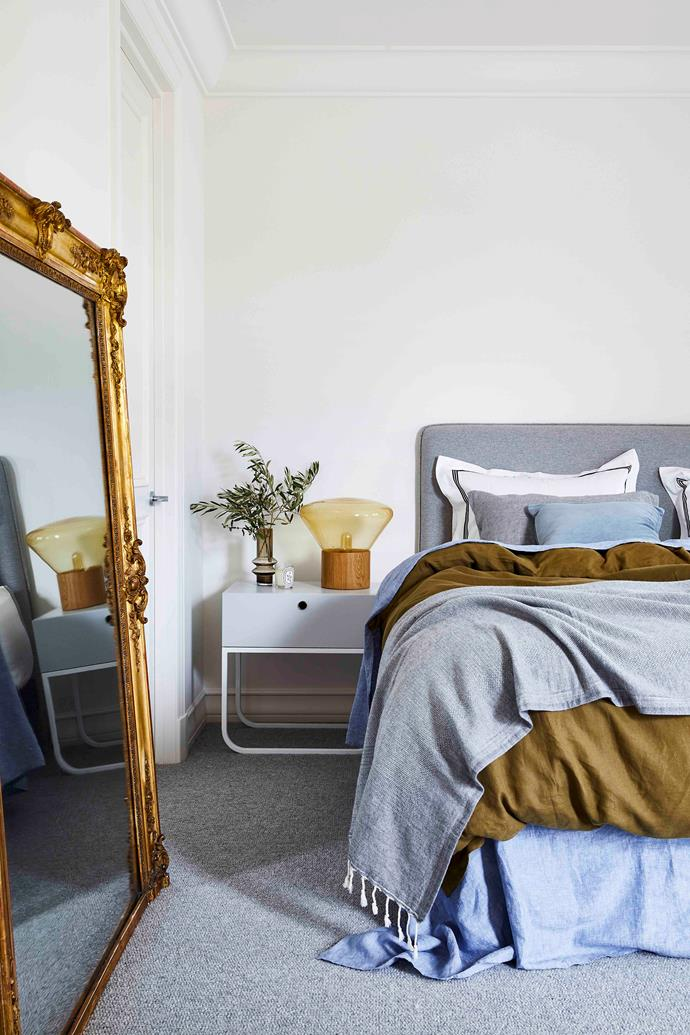 The Grazia & Co 'New York' bedside table, adorned with a Marmoset Found vessel, pairs well with a 'Frenchie' bedhead, also from Grazia & Co. The bed is dressed in linen by Sage And Clare, and the 'Muffins' oak table light by Dan Yeffet & Lucie Koldova for Brokis, sits elegantly alongside an antique gold mirror.