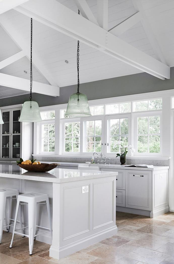 This kitchen embraces a more contemporary approach to the Hampton's style, with white cabinetry accented with against a sage green wall. Photo: Maree Homer | Styling: Kayla Gex | Story: House & Garden