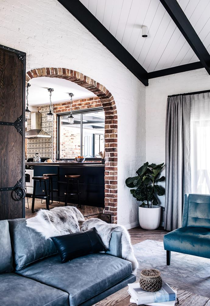 "Tasked with [transforming this Sydney home into an entertainer's dream with a modern rustic aesthetic](https://www.homestolove.com.au/modern-farmhouse-18904|target=""_blank""), interior designer Jillian Dinkel added her signature style to the abode. In the living room exposed brick walls and the vaulted ceiling were painted white, with the trusses painted pitch black for a dramatic touch. <br><br>"