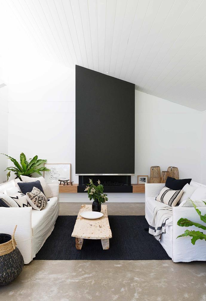 "Seeking to create a dramatic feature in the living room of this [fibro cottage](https://www.homestolove.com.au/fibro-cottage-avalon-20548|target=""_blank""), the fireplace is painted in a dark charcoal that pops against the stark white interiors that run throughout the home. A dark rug centers the living space and adds a warm contrast to the concrete flooring.<br><br>"