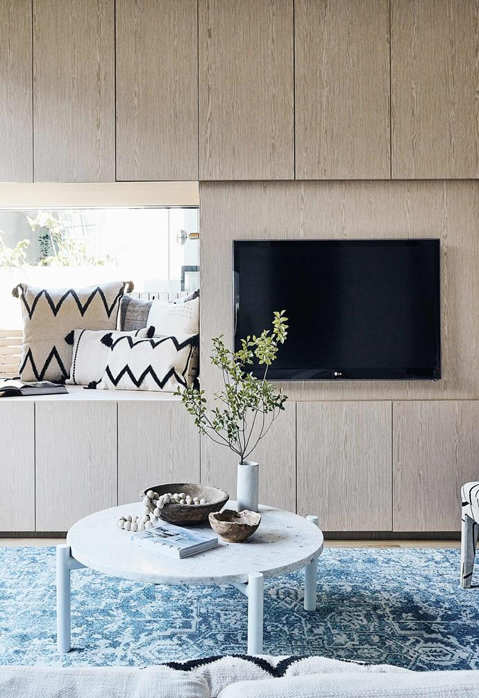 "The living room of this [coastal family home with Scandi-noir style](https://www.homestolove.com.au/scandi-noir-house-20344|target=""_blank"") features custom joinery including a clever window nook that's perfect for the kids to read in. The timber joinery adds warmth to the space and a vibrant blue rug adds a dynamic contrast.<br><br>"