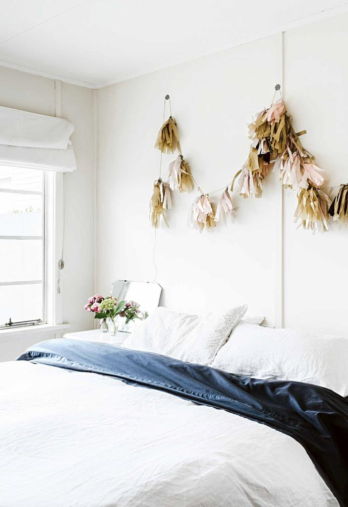 "**Lessons learnt** ""We should've integrated an outdoor kitchen… it would've been perfect as we cook on the barbecue every night,"" says Rebecca.<Br><br>**Master bedroom** Rebecca crafted this tassel garland that hangs above the bed."