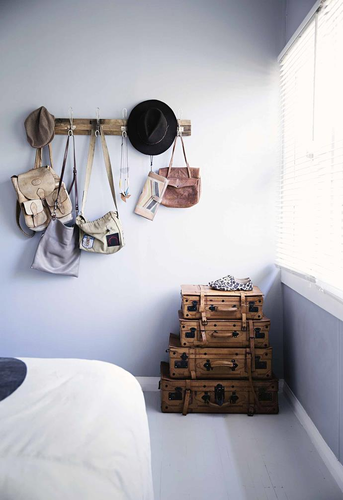 **Try hanging and stacking options to solve your storage dilemmas**<br><br>In Peta and Adrian's bedroom, a wall-mounted rack keeps bags and hats in good shape. A pile of vintage suitcases is a novel way to store out-of-season clothes or bedlinen, allowing you to keep your wardrobe free for all your current go-to clothes, bedding and other necessities. <br><br>**Tip**: Add complementary luggage tags to the suitcases as reminders of what's stored inside each one.