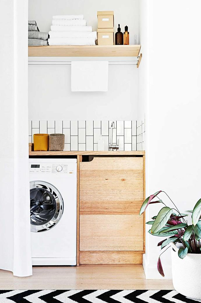"Tucked away behind a curtain, this [clever laundry nook](https://www.homestolove.com.au/laundry-inspiration-gallery-17912|target=""_blank"") features a floating shelf above the benchtop for additional storage."