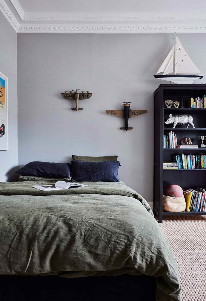 This kid's room takes a more pared-back approach to a traveller's theme. The rustic airplane models on the wall above the bed as well as the large-scale model of a yacht on the bookshelf add a playful touch.