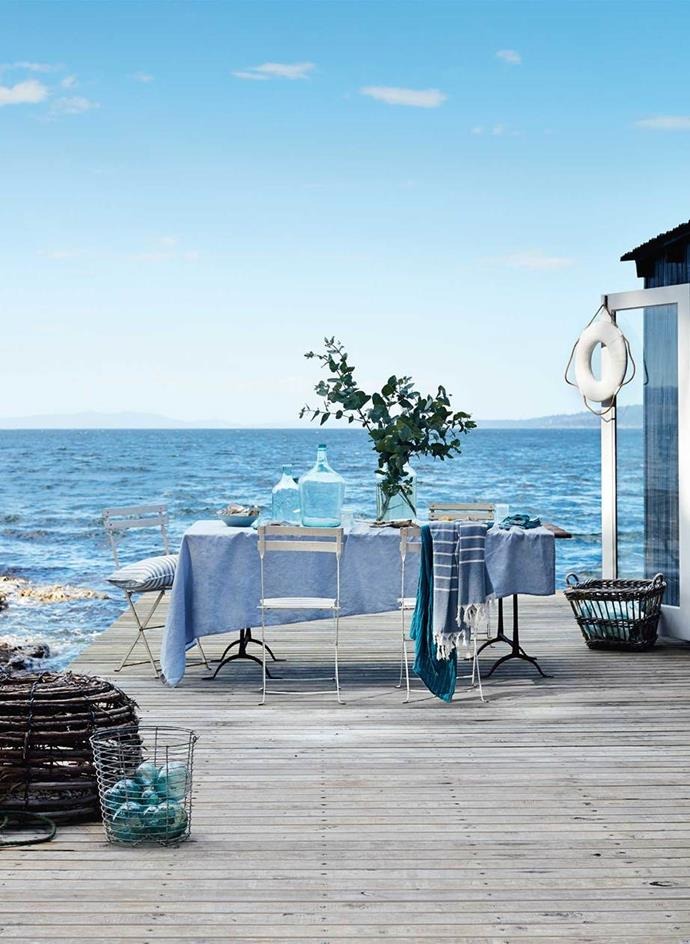 "The scene is set with a table, layered of blue linens, wire baskets, glass fishing floats and bottles at a family retreat and a guest house for hire, [Summer House](https://www.homestolove.com.au/your-own-private-island-retreat-13661|target=""_blank""), which sits on its own private island off the coast of mainland Tasmania."
