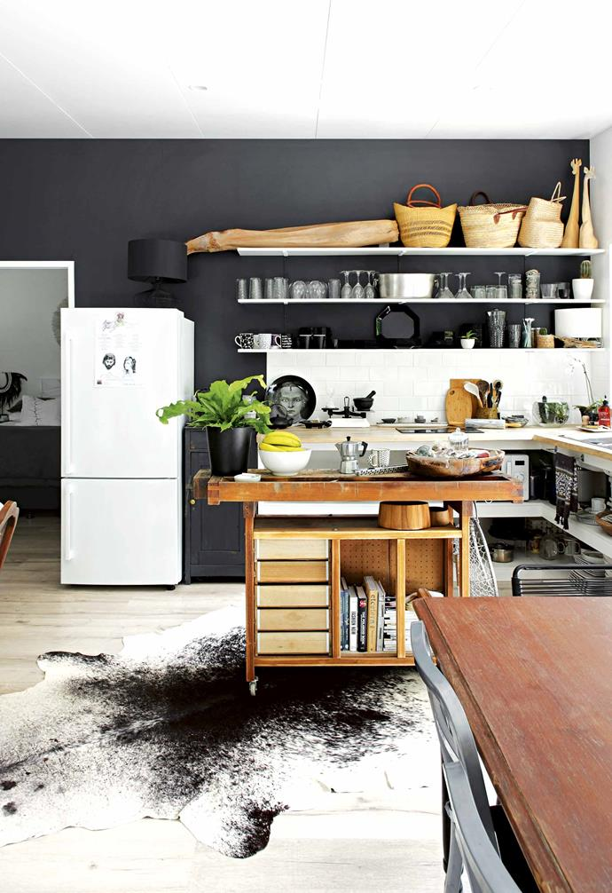 "**Don't hide it away** Here, in the kitchen, the dark charcoal of the [living room](https://www.homestolove.com.au/modern-living-room-ideas-18535|target=""_blank"") continues, creating the perfect backdrop for the open shelving that displays crockery, pans and glassware. ""I like having everything on show. My other half needs to be a bit more tidy, though."" Here, Lara has used her father's old workbench, which was a gift from her mother. ""It's an amazing piece; I can't believe I managed to get it off him. I took off the back because I like seeing the backs of the drawers."" <br><br>**Tip**: Create a flexible and open entertaining space with a portable island bench on wheels. It can first serve as a workbench and later, a drinks station."