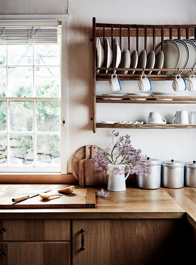 In the kitchen, Portugeuse crockery is on display in a plate rack that was bought from a market and came from a demolished Hilton hotel in East Melbourne. On the Ikea oak veneer benchtop are tins and a jug from Castlemaine Vintage Bazaar.