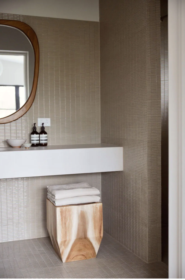Aesop toiletries are a naturally luxurious addition to the sand-hued bathroom.