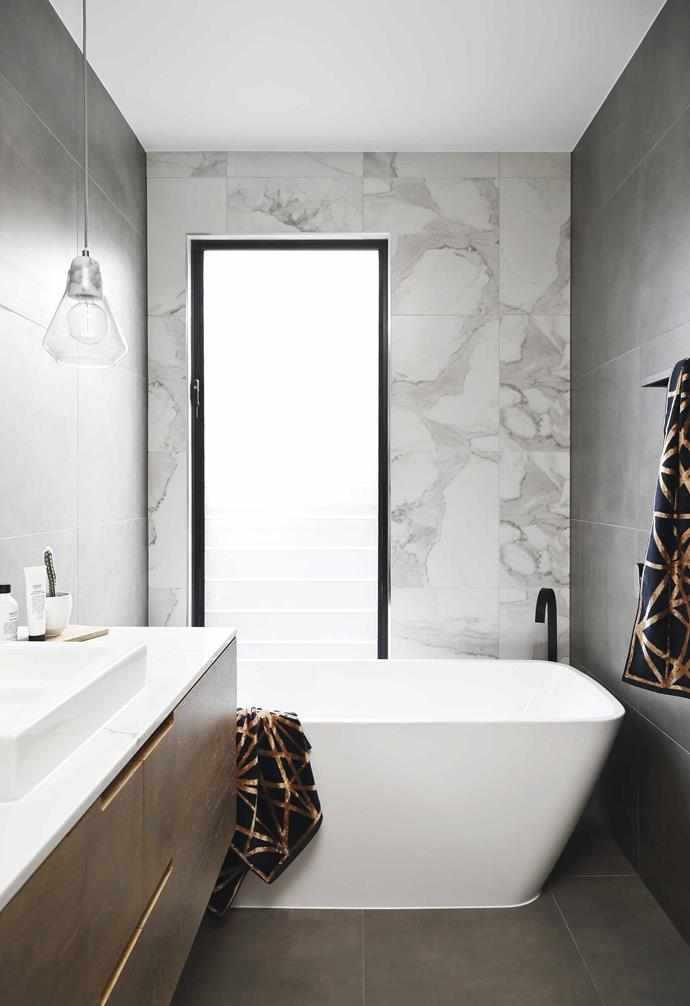 "Inspired by European barns, [this modular home in Perth](https://www.homestolove.com.au/barn-style-house-19831|target=""_blank"") features a relaxed material palette and a pared-back design. In this bathroom the louvred window is framed in black, creating a striking contrast to marble tiles and the white freestanding bathtub."