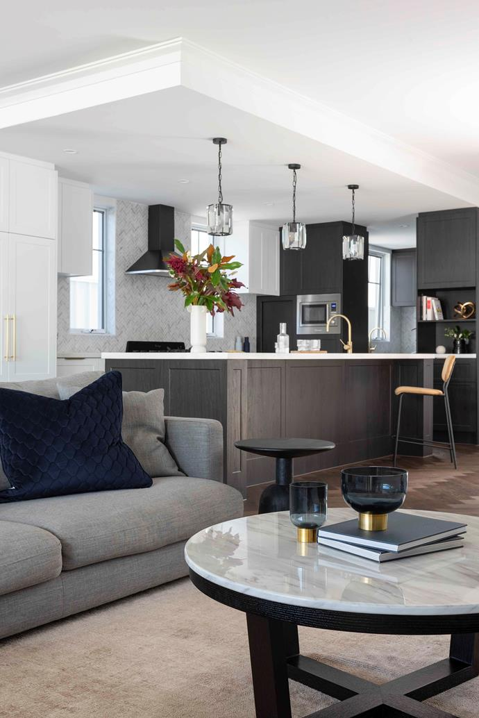 """Taking the [colour palette](https://www.homestolove.com.au/colour-scheme-tips-16173 target=""""_blank"""") through the open-plan kitchen and living area creates a sense of harmony. A marble-topped [coffee table](https://www.homestolove.com.au/coffee-table-decor-21270 target=""""_blank"""") ('Provence' by Nick Scali) with black base echoes the style of the nearby island bench. Indigo accents, such as the Marmoset Found vases (from Granite Lane) on the coffee table, also feature."""
