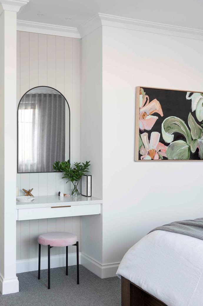 "Tucked away into a corner of Vesna and Justin's bedroom is a sophisticated make-up nook (top right) that's as practical as it is pretty. Delineated from the rest of the room care of [timber panelling](https://www.homestolove.com.au/perfect-the-scandi-style-with-timber-panelling-3847|target=""_blank"") Justin put in himself, it's painted in Dulux Tranquil Retreat to contrast with the Dulux White On White elsewhere. Pops of pink by way of a velvet stool (a lucky Kmart find, just like the arch mirror) and 'Night Garden' artwork by Alisha Falconer give the nook its [feminine feel](https://www.homestolove.com.au/gallery-master-stroke-feminine-sydney-house-design-1-2021
