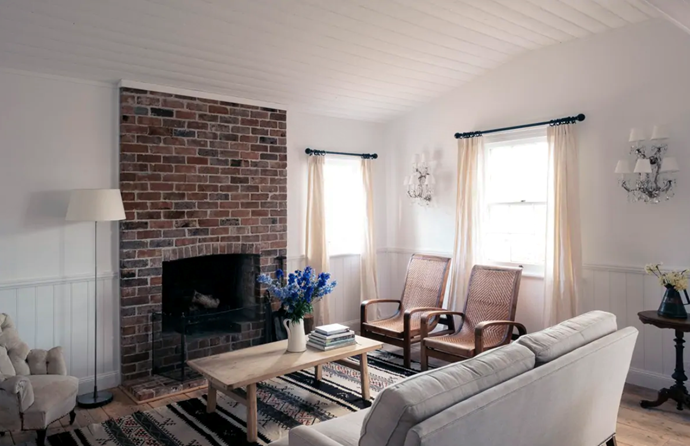 """Long drapped curtains and a warming [fireplace](https://www.homestolove.com.au/cosy-fireplaces-that-will-warm-your-heart-3475