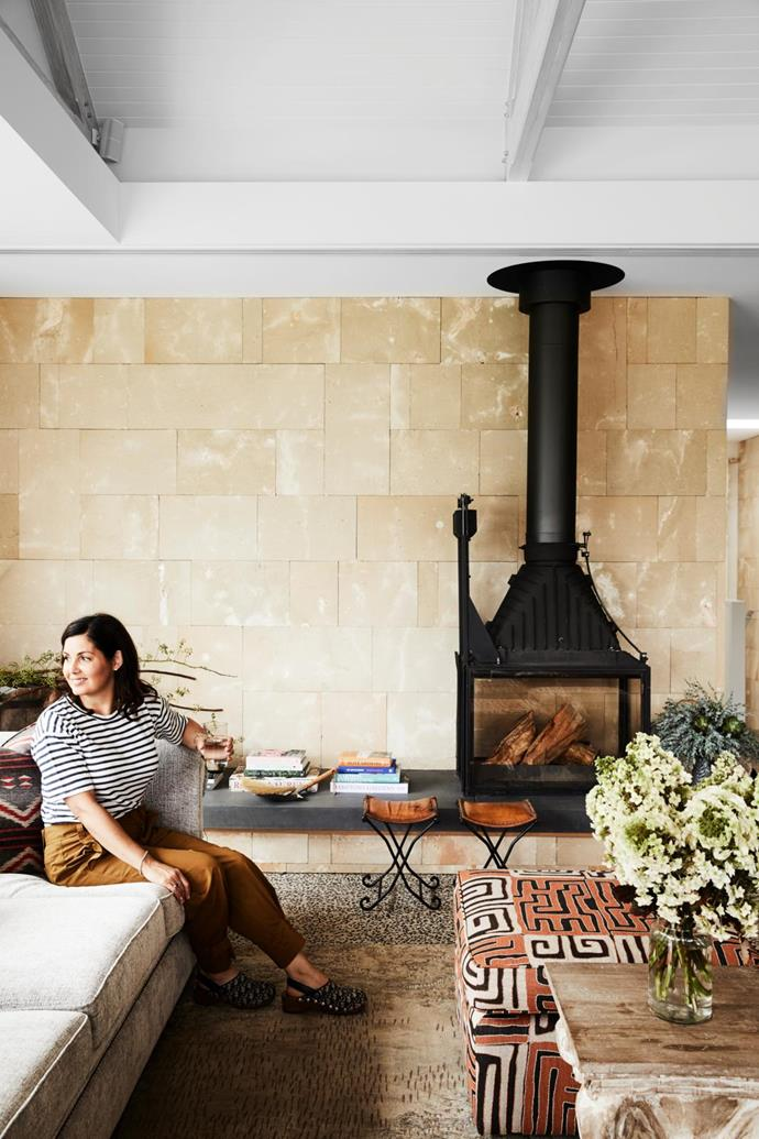 Lisa relaxes in the cosy living room. Stools, Capocchi. Limestone blocks (wall), Limestone Australia. Bluestone bench. Cheminées Philippe combustion stove, Wignells Heating & Cooking. Vintage rug, Tribe Home. Flowers by Victoria Whitelaw Beautiful Flowers (throughout).