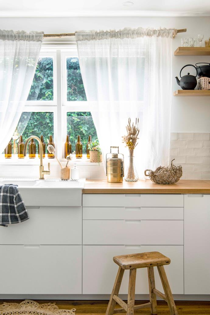 "The [kitchen](https://www.homestolove.com.au/9-kitchens-that-transcend-design-trends-6574|target=""_blank"") pays homage to Mei's love of natural materials, with a splashback of hand-pressed 'Mood Bianco' subway tiles from Art Of Tiles and breezy Ikea linen curtains drawn across a Uniqwa eucalyptus pole. A row of amber Rekorderlig bottles along the windowsill throws golden light into the room, while the brass mixer by Candana is a gleaming metallic accent."