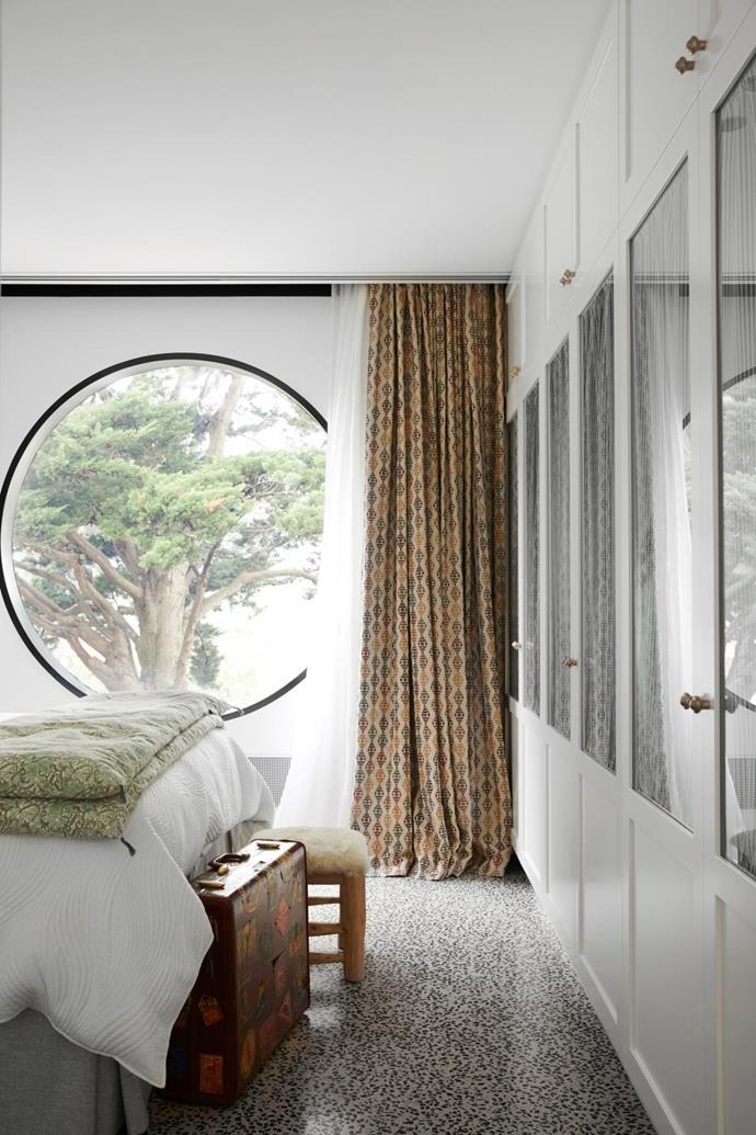 The round window frames tree views. Curtains in a Pierre Frey fabric. Stool, Fenton & Fenton. Door hardware, Pittella.